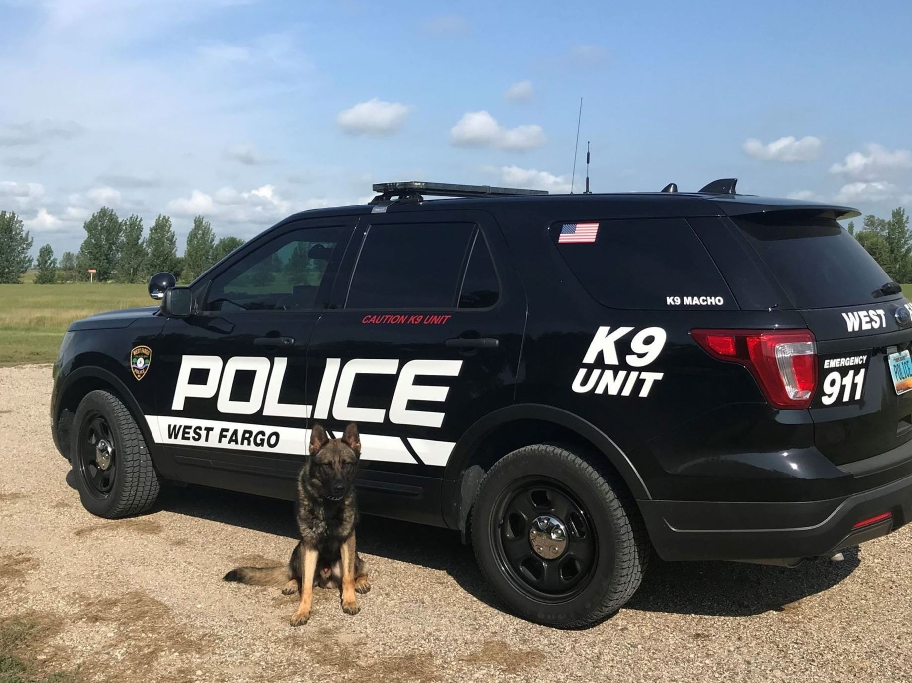 West Fargo Police Department K9 Macho poses in front of K9 unit vehicle